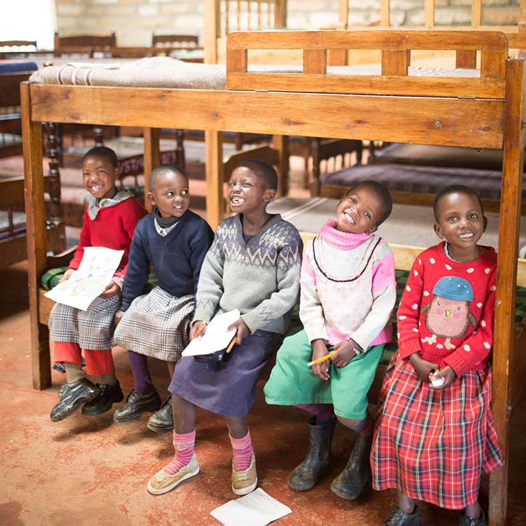 girls at Our Lady of Grace Children's Home sitting on their bunk beds