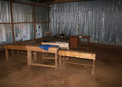 Desks on a dirt floor with metal walls which is a kindergarten class for Our Lady of Grace School in Kenya